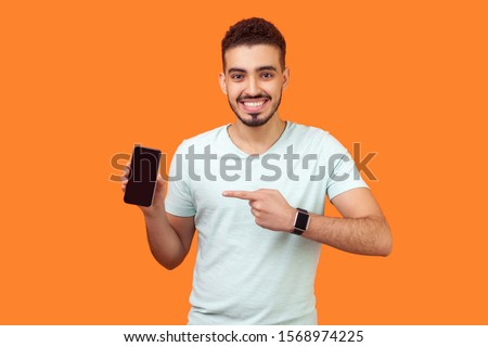 Portrait of satisfied brunette man with beard in white t-shirt pointing at cellphone and smiling at camera, recommending gadget or mobile application. indoor studio shot isolated on orange background