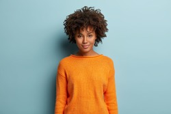 Portrait of satisfied dark skinned female model with Afro haircut, gentle smile, dressed in casual orange jumper, looks straightly at camera, pose over blue studio wall for making photo. Ethnicity