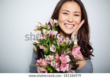 Portrait of satisfied woman with bunch of flowers looking at camera