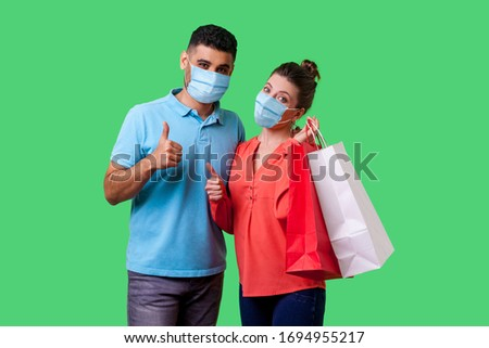 Portrait of satisfied young couple with surgical medical masks showing thumbs up gesture together, cute woman holding bags and smiling. isolated on green background, indoor studio shot