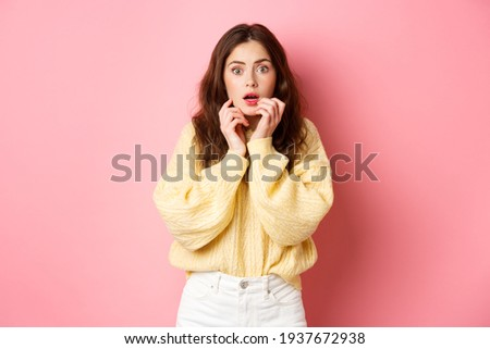 Portrait of scared and shocked brunette girl, gasping and holding hands near lips, staring frightened at camera, standing startled against pink background Stockfoto ©