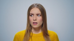 Portrait of scared girl looking on grey background. Closeup disappointed woman posing in slow motion. Worried lady shocked at camera. Upset female model standing in studio.