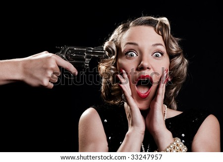 portrait of scared woman against black background