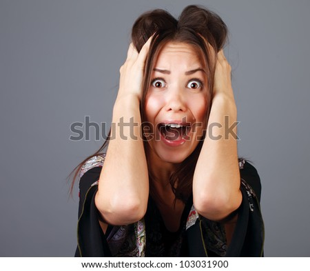 portrait of scared woman against dark background