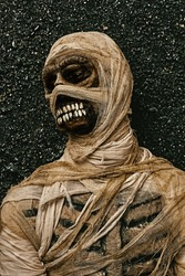 Portrait of scary evil mummy on green dark background. Halloween. Ancient Egyptian mythology.