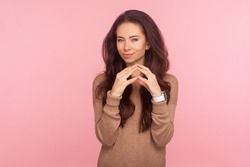 Portrait of scheming devious attractive young woman with brunette hair clasping hands and thinking over tricky plan, having sly cunning idea to prank. indoor studio shot isolated on pink background