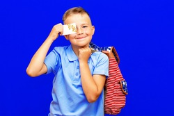 Portrait of school boy in blue t shirt uniform backpack hold in hand credit bank card isolated on bright blue background children studio portrait.