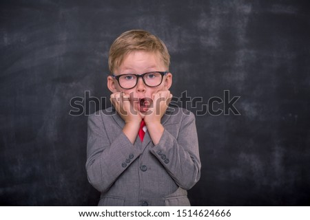 Portrait of school boy in glasses with funny shocked face expression isolated on background. Back to school.