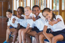 Portrait of school kids showing thumbs up in basketball court at school