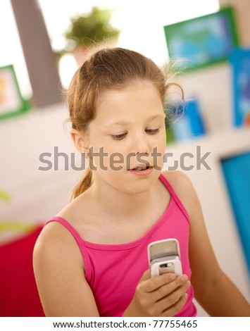 Portrait of schoolgirl using cellphone at home? - stock photo