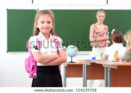 portrait of schoolgirl with a school backpack, in the background a classroom and the teacher tells the class