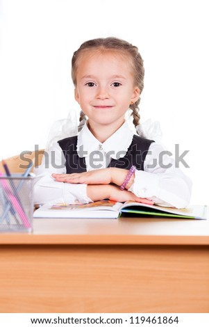 Portrait of schoolgirl with book sitting at  the classroom