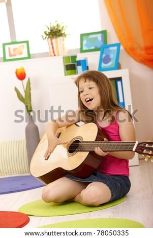 Portrait of schoolgirl with guitar, singing, sitting on living room floor.?