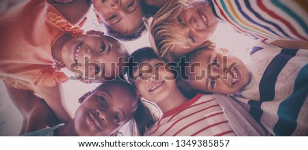 Portrait of schoolkids forming huddle on a sunny day