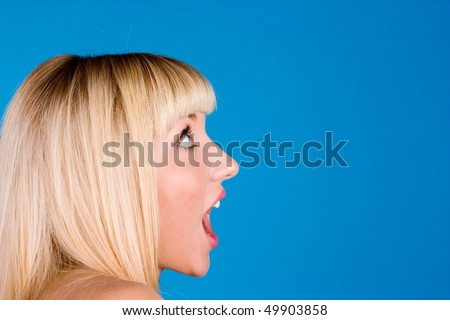 Portrait of screaming woman isolated on blue background