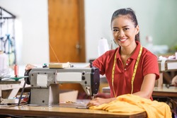 portrait of Seamstress in textile factory smiling while  sewing with industrial sewing machine at garment