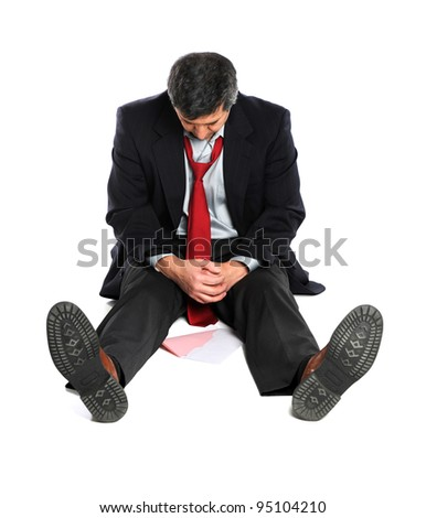Portrait of seated businessman in despair with pink slip on floor isolated over white background