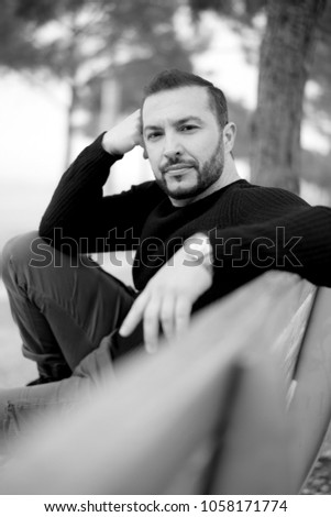 Portrait of Self Confident Man wearing casual clothes sitting on a bench at a park outdoors, black and white photo #1058171774