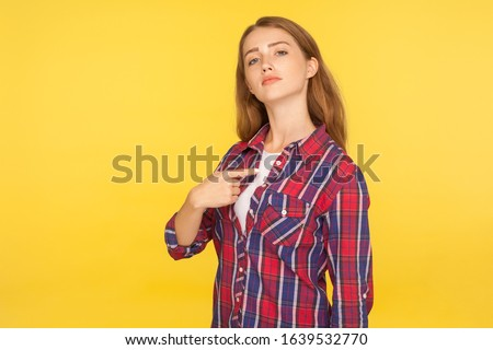 Portrait of selfish haughty ginger girl in checkered shirt pointing at herself, looking at camera with arrogance and pride, egoistic person. studio shot isolated on yellow background Stock photo ©