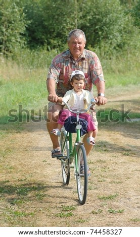Portrait of senior and baby on the bicycle