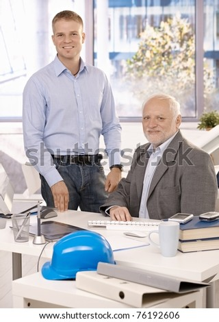 Portrait of senior and junior businessmen working in office, looking at camera, smiling.?