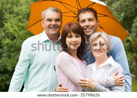 Portrait of senior and young couples under umbrella outdoors