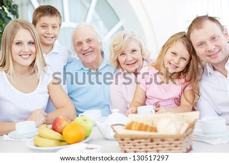 Portrait of senior and young couples with their children having dinner at home