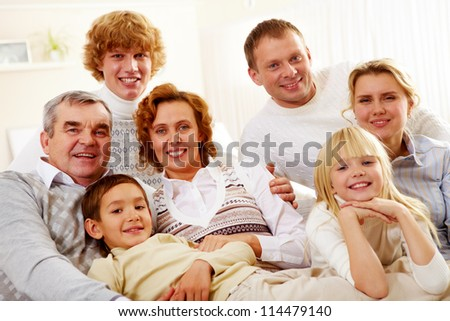 Portrait of senior and young couples with their children relaxing at home