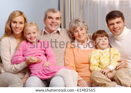 Portrait of senior and young couples with their children sitting on sofa at home