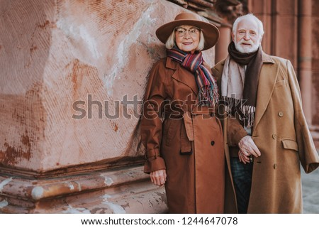 Portrait of senior bearded man and his wife standing near old building. They looking at camera and smiling