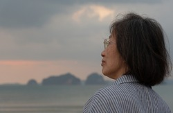 portrait of senior beautiful asian retired lonely woman looking at ocean at sunset in moody day