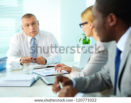 Portrait of senior boss looking at his employees at meeting