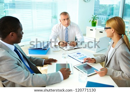 Portrait of senior boss talking and his employees at meeting