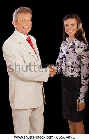 portrait of senior businessman and young woman secretary shaking hands on black