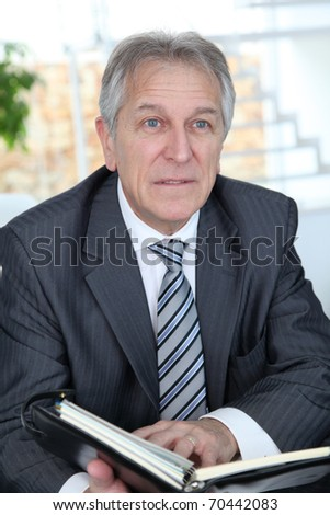Portrait of senior businessman holding agenda