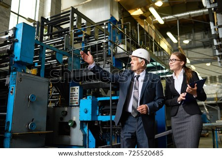 Portrait of senior businessman or executive manager wearing hardhat touring modern factory with young assistant