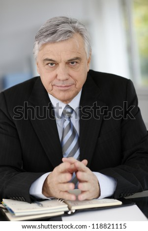 Portrait of senior businessman sitting at desk