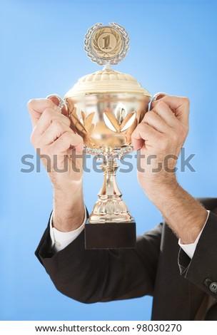 Portrait of senior businessmen holding a trophy on sky