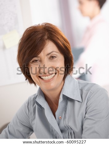Portrait of senior businesswoman smiling at camera, coworker in background.?