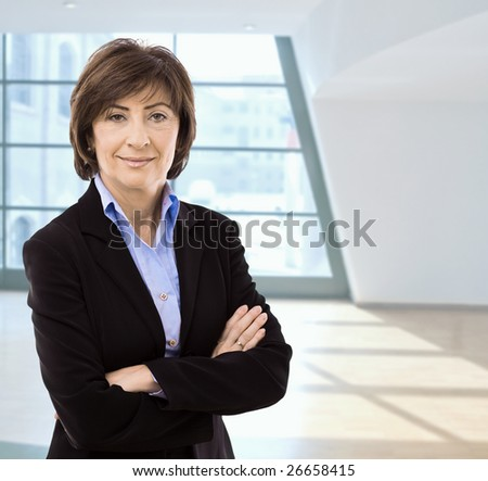 Portrait of senior businesswoman standing with arms crossed in office hall, smiling.