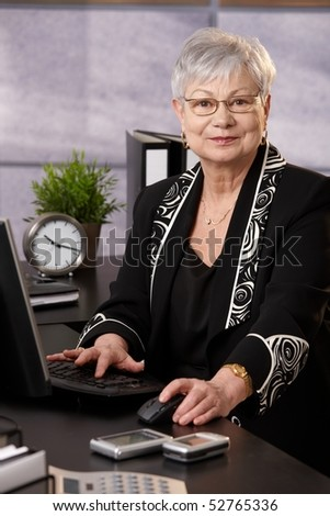 Portrait of senior businesswoman working with computer at desk in office, looking at camera, smiling.