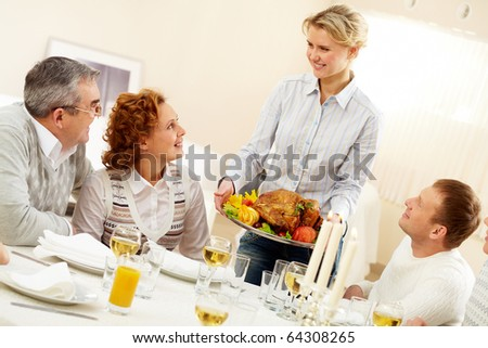 Portrait of senior couple and happy man pretty woman with roasted turkey going to put it on festive table