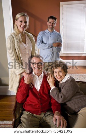 Portrait of senior couple at home on sofa with adult children