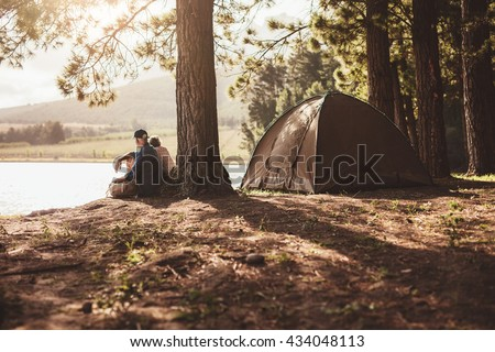 Portrait of senior couple camping by a lake. Man and woman sitting under a tree looking away a the lake on summer day.