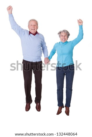 Portrait Of Senior Couple Jumping In Joy Over White Background