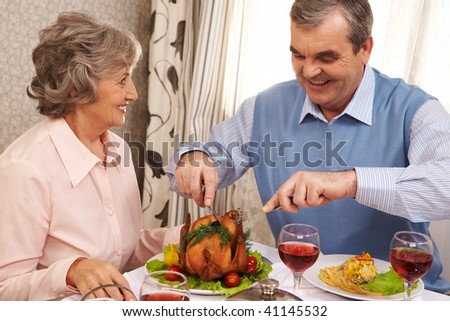 Portrait of senior couple sitting at Christmas table while happy man cutting roasted turkey