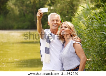 Portrait of senior couple sitting at lakeside. Elderly man hugs her wife while take self portrait with mobile.