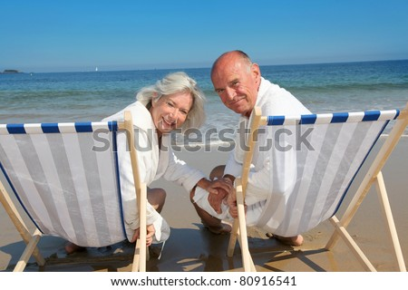Portrait of senior couple sitting in deckchairs - stock photo