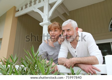 Portrait of senior couple standing in front of their home - stock photo