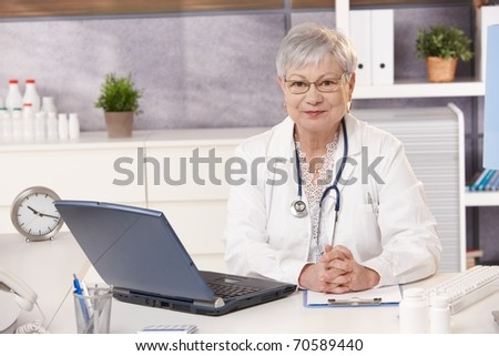 Portrait of senior doctor at work, looking at camera, sitting at desk.? - stock photo